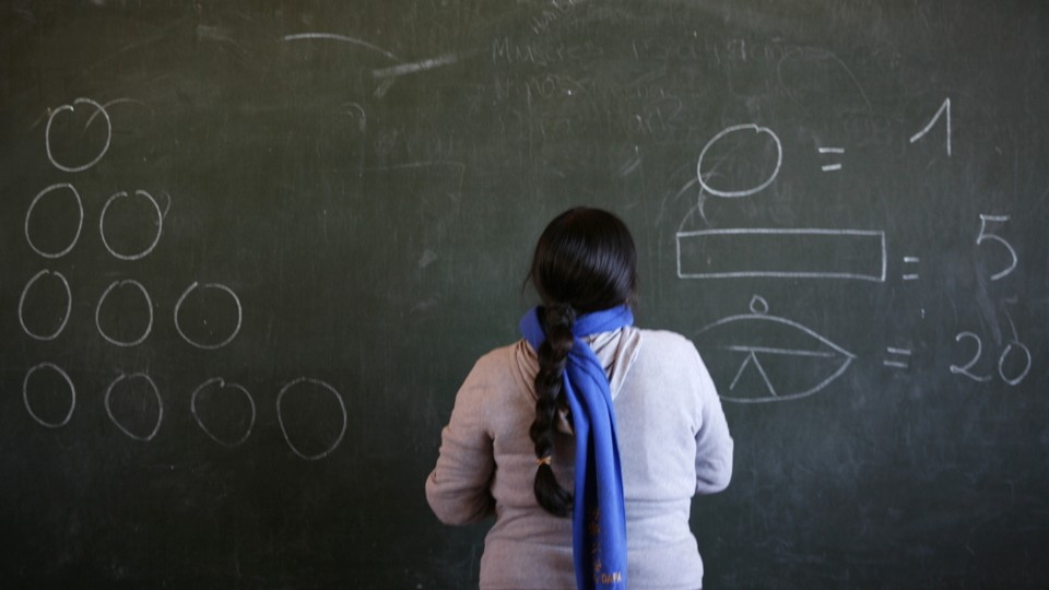 A teacher faces a chalkboard with numbers and shapes on it.