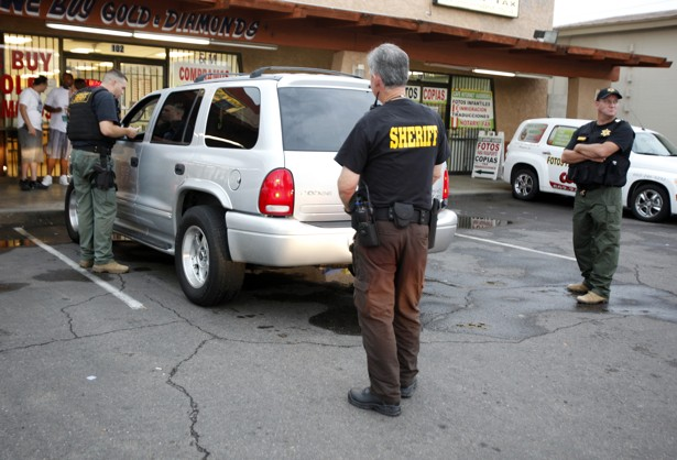 Maricopa County Sheriffs stop a vehicle for a traffic violation during a crime sweep in Phoenix.