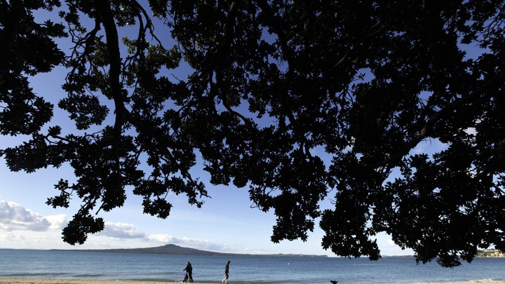 People walk along Kohimarama Beach in Auckland in 2011.