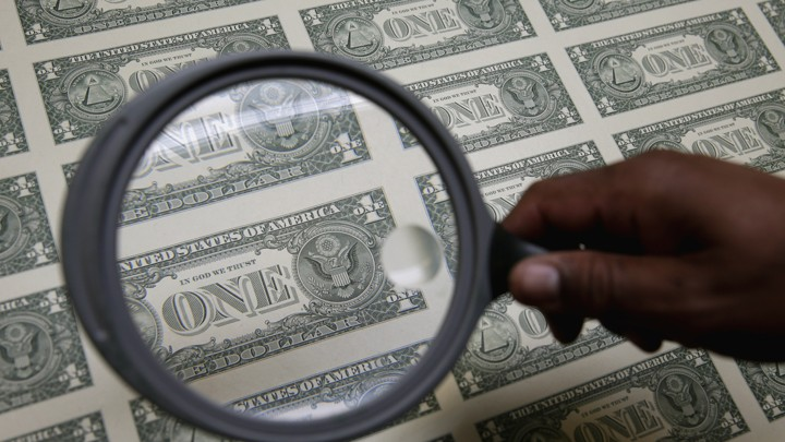A magnifying glass hovers over a sheet of one-dollar bills.