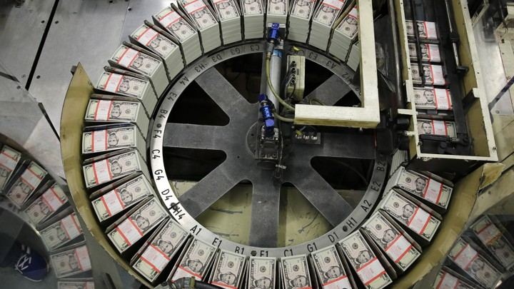 Stacks of $5 bills sit on a circular conveyor belt.