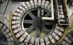 Stacks of $5 bills sit on a circular conveyor belt.