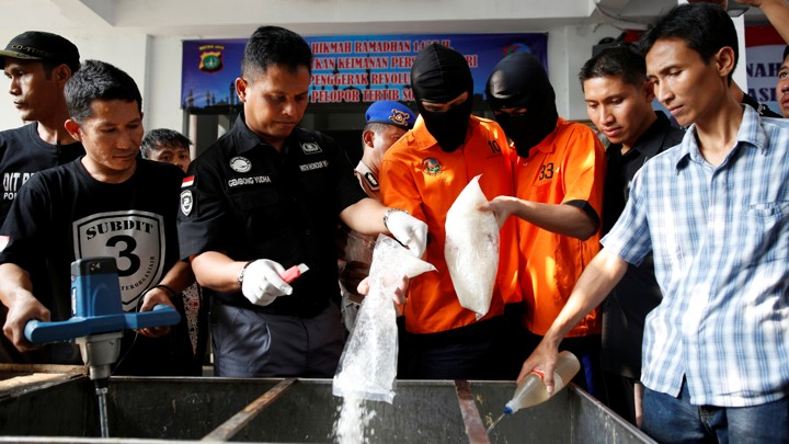 Recently arrested drug trafficking suspects are forced to take part in the destruction of illegal narcotics in Indonesia.