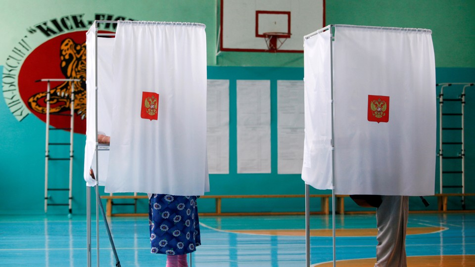 People stand inside voting booths as they visit a polling station during a  parliamentary election in Stavropol, Russia, September 18, 2016.