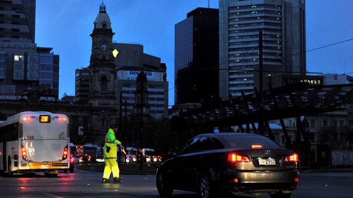 A traffic policeman directs vehicles in the blackout in Adelaide, Australia, on Wednesday.