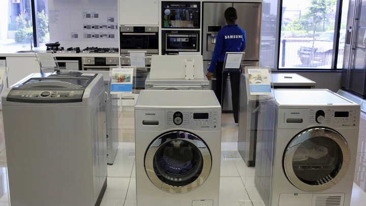 Samsung washing machines are seen as an employee inspects refrigerators at a Samsung display store in Johannesburg, October 3, 2013