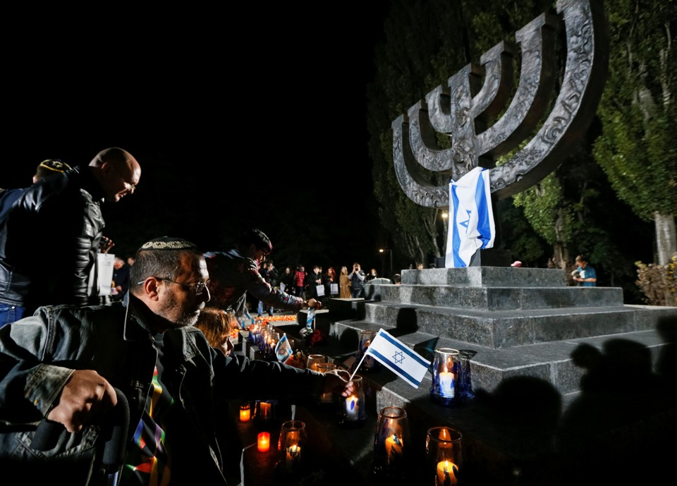 People place candles and Israeli flags during a ceremony commemorating the victims of Babi Yar on September 29, 2016.