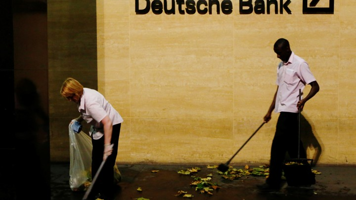 Workers sweep leaves outside Deutsche Bank offices in London, Britain December 5, 2013.