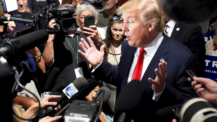 Donald Trump is surrounded by reporters holding cameras and microphones as he addresses the media during the National Federation of Republican Assemblies, in Nashville, in 2015.