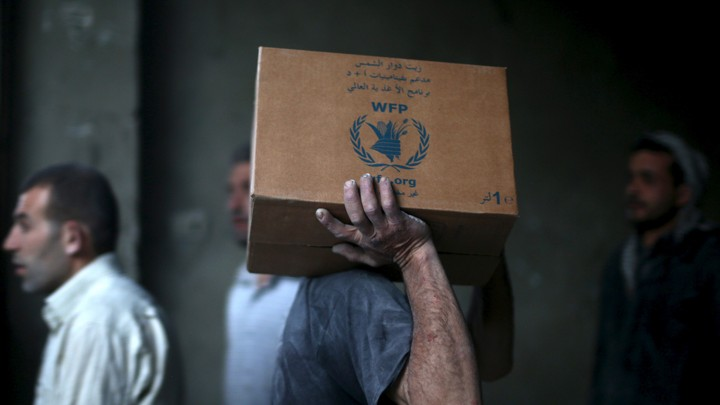 A man unloads boxes from an aid convoy in eastern Damascus, Syria.