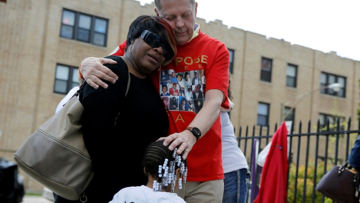 Michael Pfleger, a Chicago priest and voice in the anti-violence movement in the city, comforts the family of a shooting victim earlier this year.