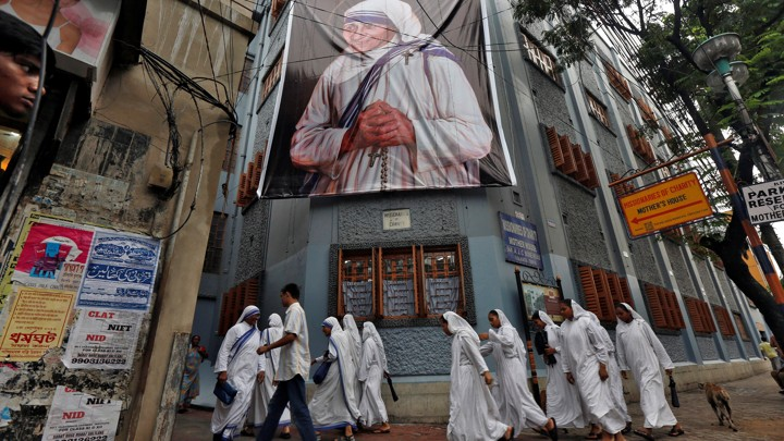 Nuns walk past a large banner of Mother Teresa ahead of her canonization ceremony in Kolkata, India, on September 4, 2016.