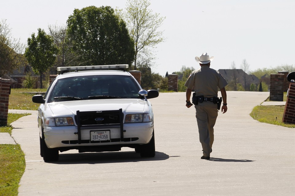 On a sunny day, a sheriff's deputy in a beige uniform, with his back to the photographer, walks alongside his gray squad card.