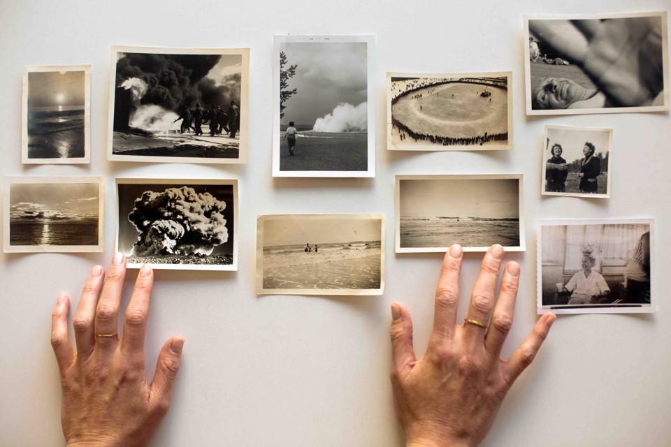 Amelia Walker's hands hover over her collection of snapshots.
