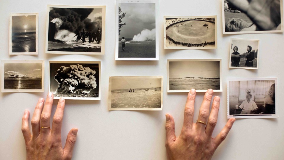 Amelia Walker's hands hover over her collection of snapshots.