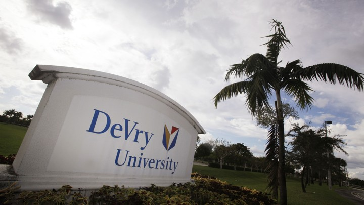 "A sign reading ""DeVry University"" sits next to a palm tree in Florida."