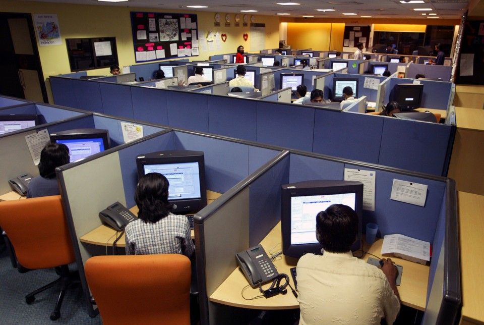 Office workers sit at cubicles in a call center