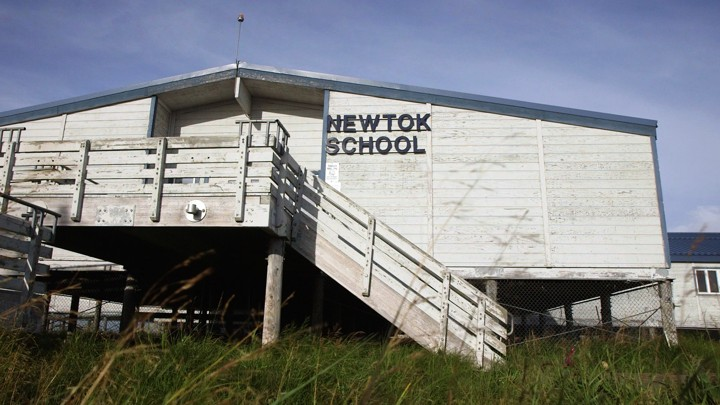 Newtok School is white and sits on risers about eight feet above the ground.