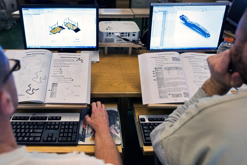 Two students look at technical drawings on computers.