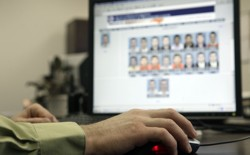 An officer looks through photos in a federal facial-recognition system