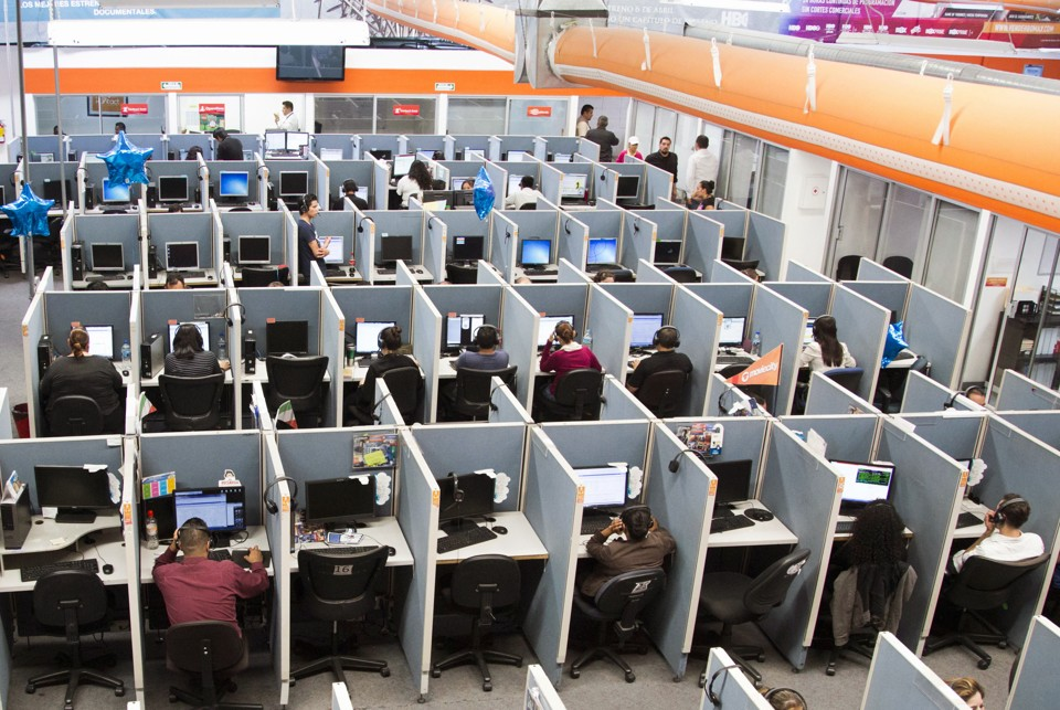 Workers sit at desks in a call center