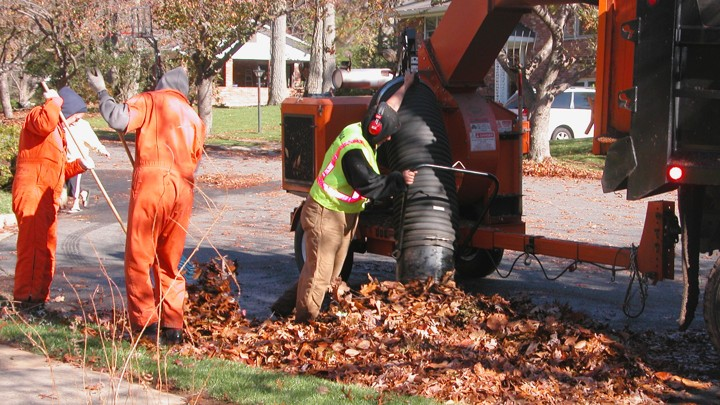 Workers clean up leaves on a suburban street.