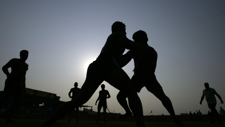 A silhouetted picture of Indian and Pakistani players as they compete in a Kabbadi match.