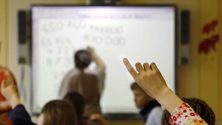 A student raises her hand as her teacher leads a lesson on a SmartBoard. Questions are being raised about whether teachers should be paid for the lessons they create.