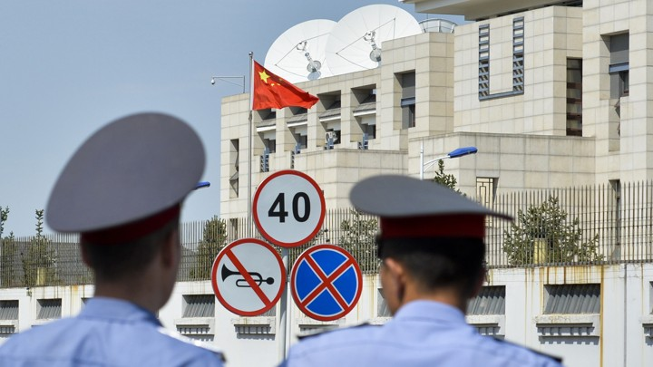 Kyrgyz police officers look at the Chinese Embassy after a suicide bombing in Bishkek, Kyrgyzstan.