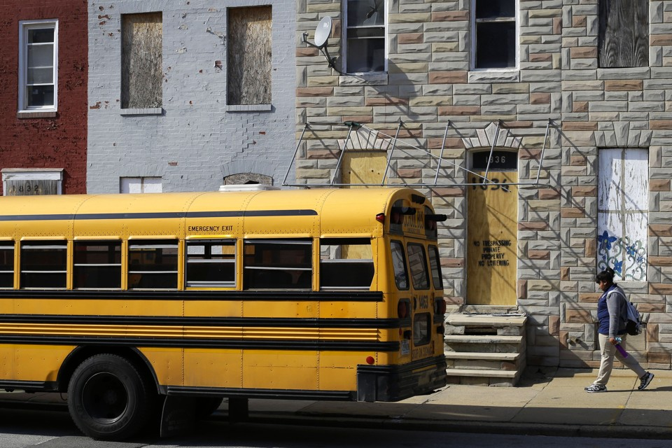 A student walks past vacant row houses to a waiting school bus as school gets out for the day in Baltimore.
