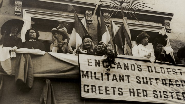 "Elizabeth Wolstenholme Elmy by a banner that reads ""England's Oldest Militant Suffragist Greets Her Sisters"""