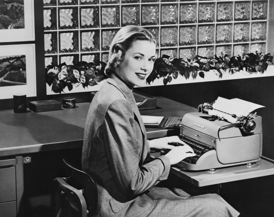 The actress Grace Kelly sitting at a table with a Remington typewriter