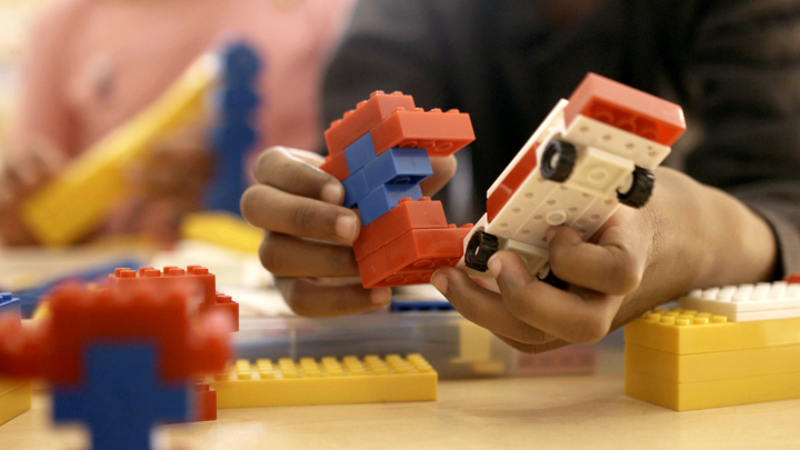 A pair of hands plays with figures made out of Legos.
