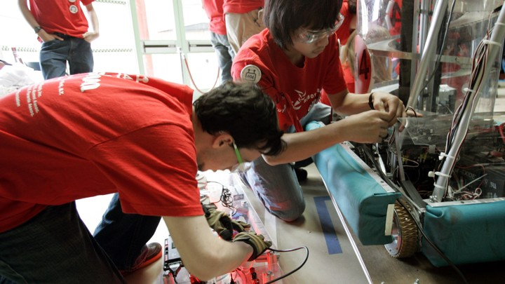 Two students work on a robot.