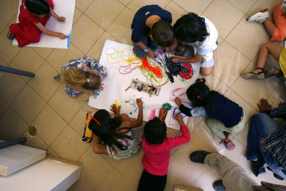 An overhead view of six pre-schoolers coloring.