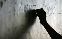 A silhouette hand writes on a chalkboard.
