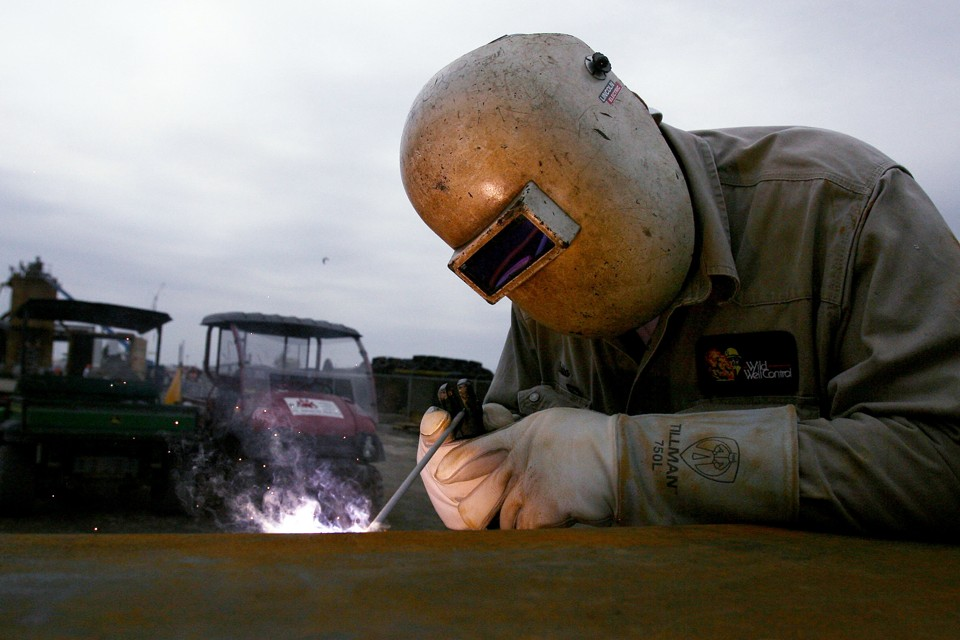 A welder works with a small torch and helmet on.