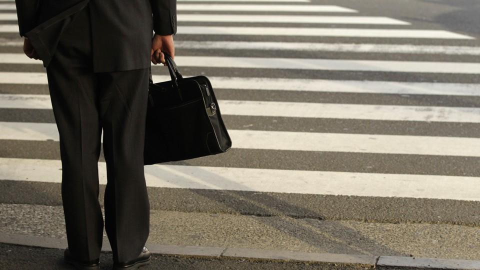 A businessman waits on a street corner.