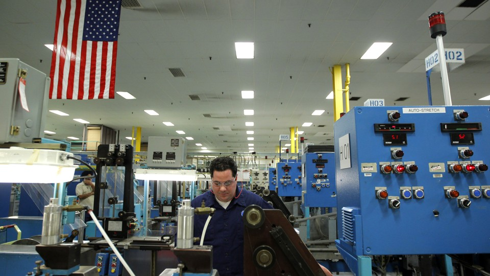 A man works in a factory among several machines.