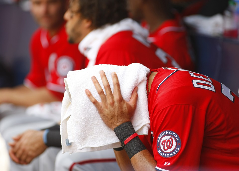 Washington Nationals shortstop Ian Desmond drapes a towel over his head to cool off in 100-degree heat.