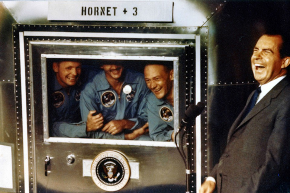 The Apollo XI astronauts Neil Armstrong, Michael Collins, and Buzz Aldrin laugh with President Richard Nixon aboard the USS Hornet in 1969.