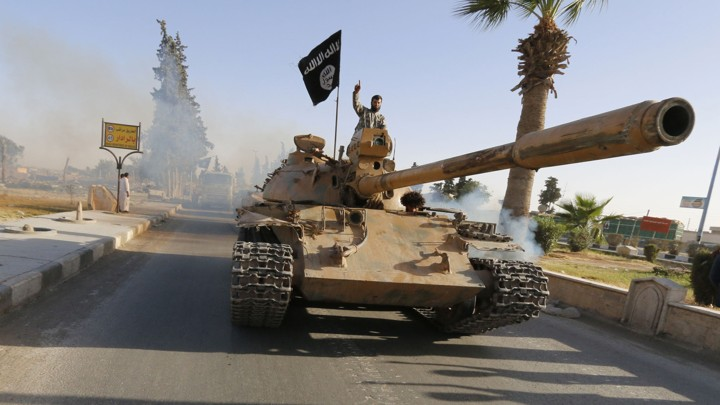 Militant Islamist fighters on a tank take part in a military parade along the streets of northern Raqqa province June 30, 2014.