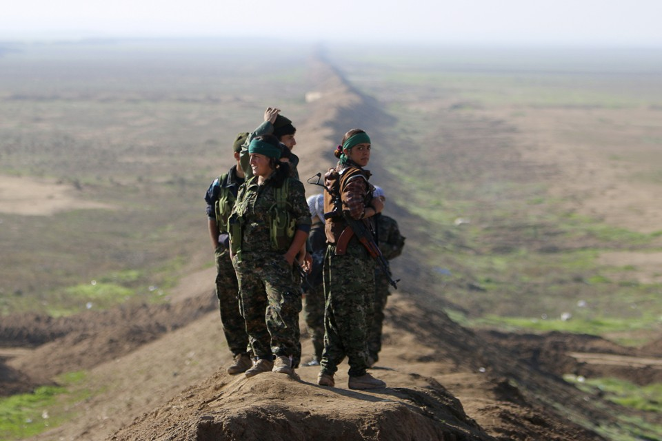Female fighters of the Kurdish People's Protection Units (YPG) stand near the border between Syria and Iraq, December 22, 2014.