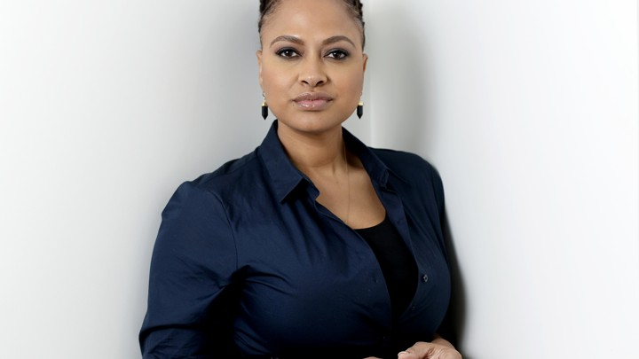 Ava DuVernay stands against a white background in a dark blue shirt