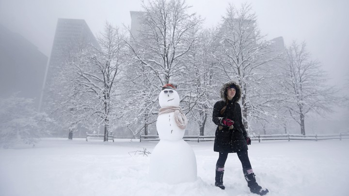 A woman wearing a heavy winter coat walks past a snowman she built in a park during blizzard conditions in Chicago, in 2015.