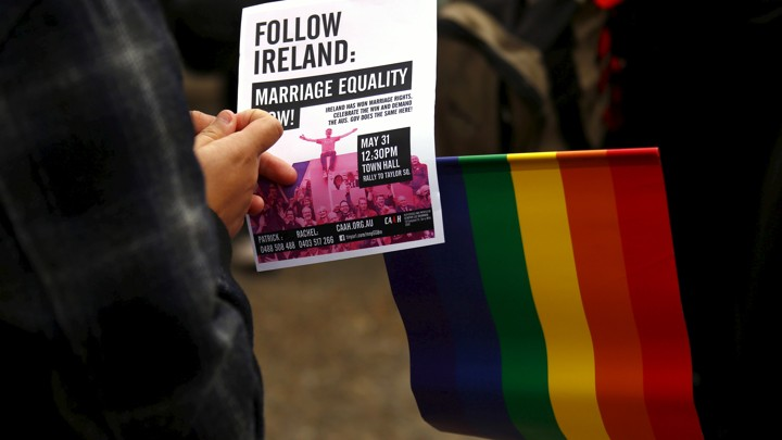 Activists hold signs in support of same-sex marriage in Australia.