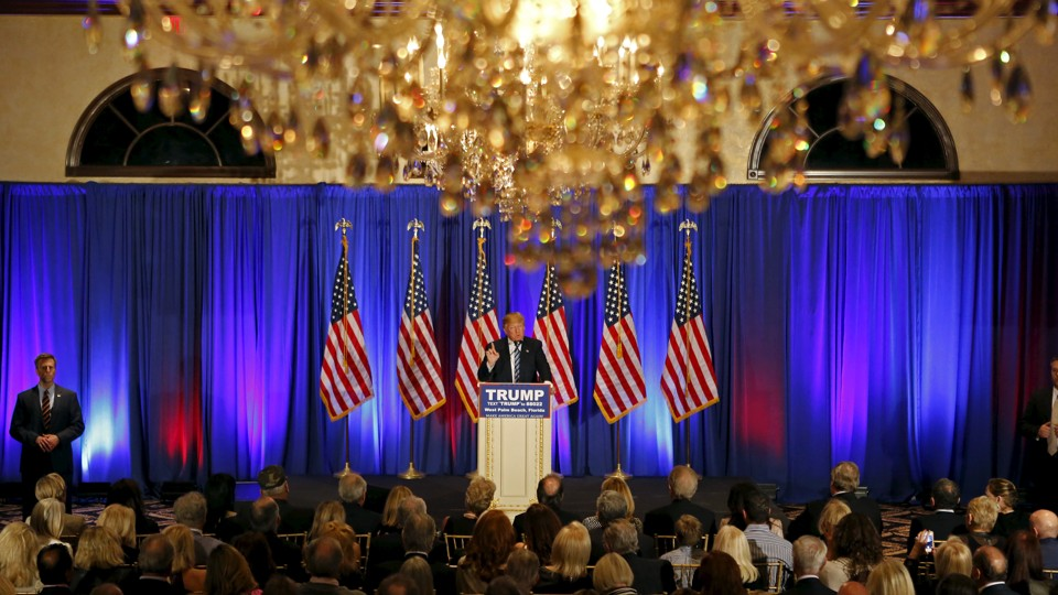 Donald Trump speaks beneath chandeliers at a press event at his Trump International Golf Club in West Palm Beach in March.