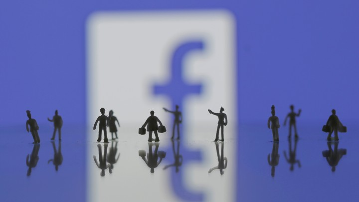 Several human minifigures stand in front of the Facebook logo