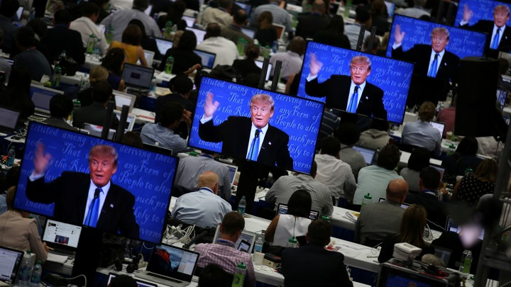 Reporters watch Donald J. Trump on television screens during the first presidential debate.