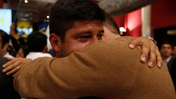 "Two men hug and cry after the nation votes ""no"" on the recent FARC referendum."